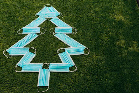 Christmas Tree Made of Blue Medical Masks on a Green Background with Copy Space