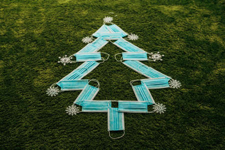 Christmas Tree Made of Medical Masks on a Green Background