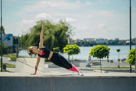 Girl doing exercises on a sports field by the lake. Healthy lifestyle concept.