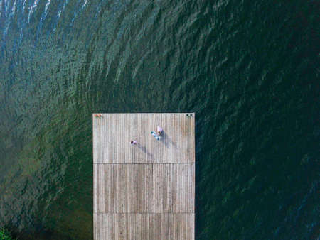 Two girls sing on a wooden pier. Air view. SurrealismThe concept of a healthy and optimistic lifestyle Zdjęcie Seryjne
