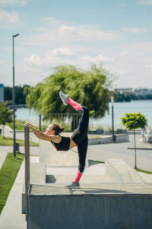 Girl athlete is engaged in yoga on the site by the lake..