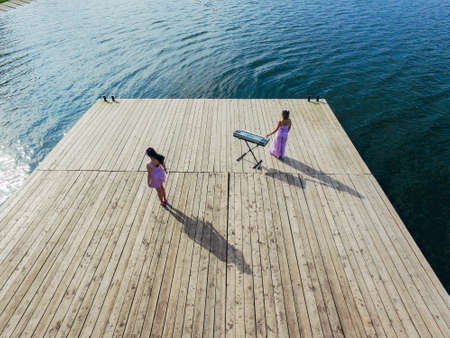 Aerial view. Two girls are standing with yonika on the pier. Surrealism