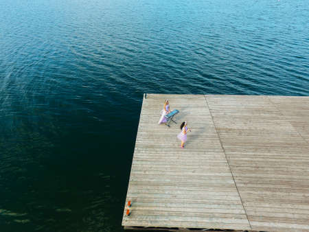 Aerial view. Two girls are sing on the pier. Surrealism. Zdjęcie Seryjne