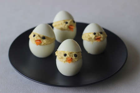 Devilled egg chicks prepared as Easter Eggs. Traditional celebration of making eggs as the symbol of new life and resurrection. Shot on white background
