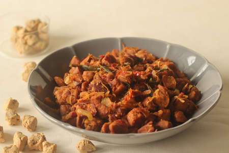 Dry roasted soya chunks with onions tomatoes and spices. Prepared with Kerala style meat masala in coconut oil. Shot on white background Foto de archivo