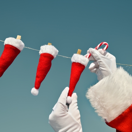 nice surprice - Santa Claus filling candy cane in mini Santa Hats that are hanging on a clothesline  photo