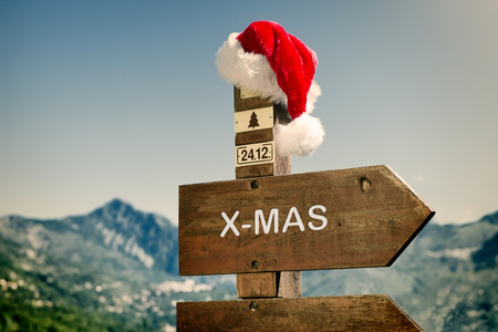 Towards Christmas - Signpost with Santa Hat against a mountain landscape   photo