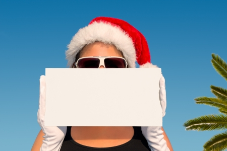 Hot Christmas Vacation - Attractive woman with santa hat holding a sign  photo
