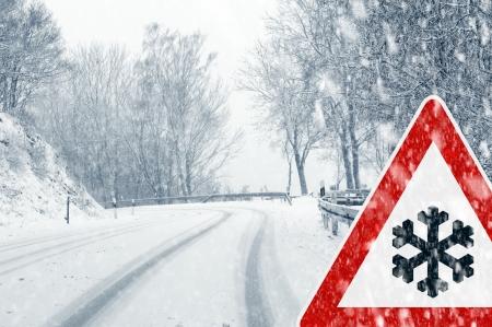 Besneeuwde bochtige weg met verkeersbord - Plotselinge en hevige sneeuwval op een landweg Rijden op het gevaarlijk wordt