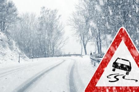 Besneeuwde bochtige weg met verkeersbord - Plotselinge en zware sneeuwval op een landweg Rijden op het wordt gevaarlijk Stockfoto