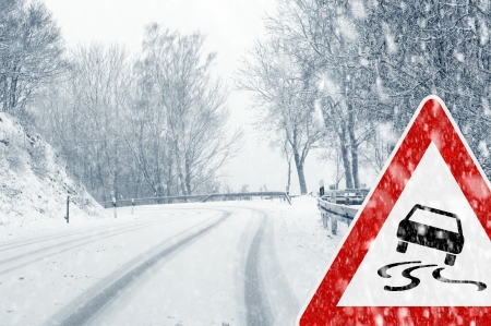 cautious: Snowy curvy road with traffic sign - Sudden and heavy snowfall on a country road  Driving on it becomes dangerous