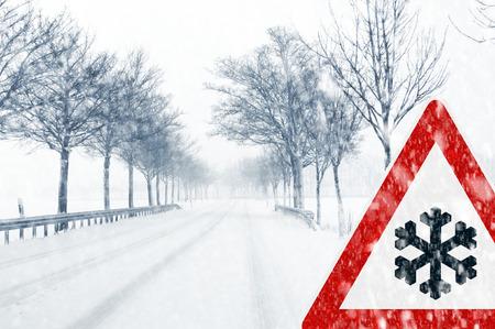 Besneeuwde weg met verkeersbord - Plotselinge en zware sneeuwval op een landweg Rijden op het wordt gevaarlijk