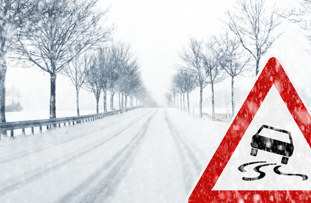 cautious: Snowy road with traffic sign - Sudden and heavy snowfall on a country road  Driving on it becomes dangerous