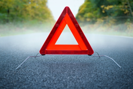 Caution fog - Warning triangle on a foggy road photo