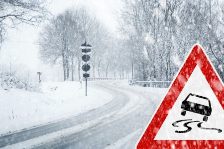 slippery: Snowy curvy road with traffic sign