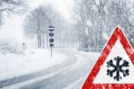 Besneeuwde bochtige weg met verkeersbord