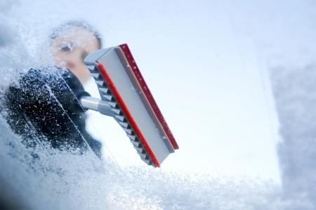 rijden in de winter - de vrouw schrapen ijs van een voorruit
