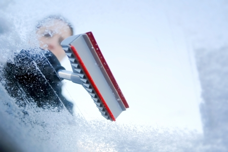 the car window: winter driving - Woman scraping ice from a windshield