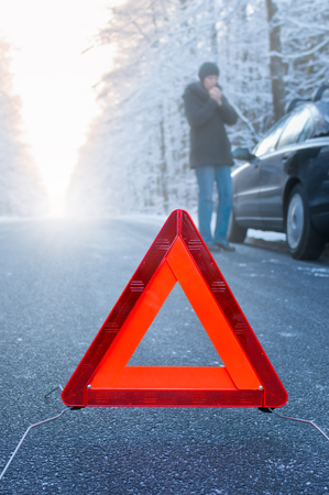 Winter driving - Car breakdown on a country road in winter  Woman standing beside her car and waiting for help  photo