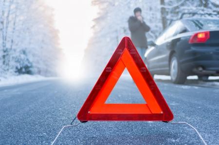 冬の運転 - 冬の国の道路で車の故障助けを待っている女性は彼女の車の横に立っています。 写真素材