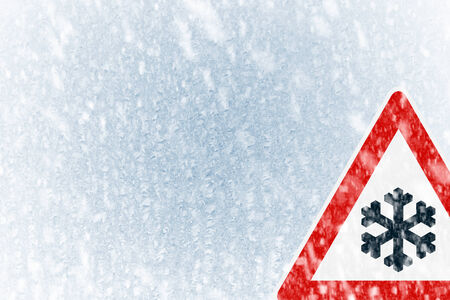 space weather tire: Winter driving - Snow on an ice covered windshield with copy space and warning sign Stock Photo
