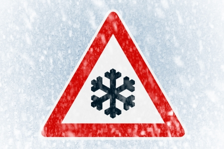 Winter driving - Snow on an ice covered windshield with warning sign Stock Photo