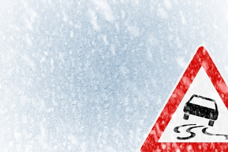 Winter driving - Snow on an ice covered windshield with copy space and warning sign photo