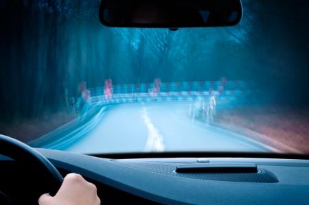's nachts rijden - let op, rijden op een bochtige landweg Stockfoto