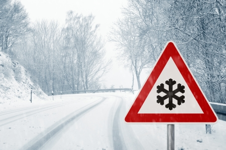 winter driving - snowy country road in winter - warning sign