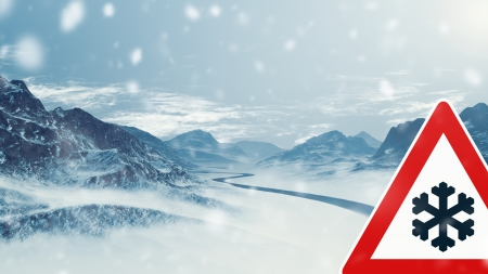 over black: winter driving - caution - country road winding through a winter mountain landscape  Stock Photo