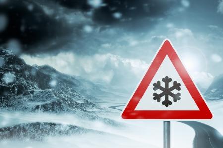 winter driving - caution - country road winding through a winter mountain landscape  Foto de archivo