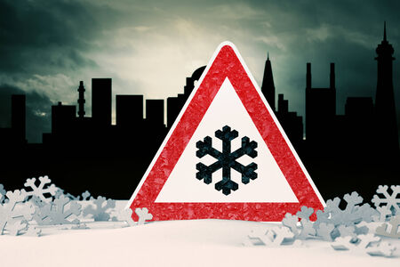 Caution - snow in the city - traffic sign against city skyline photo