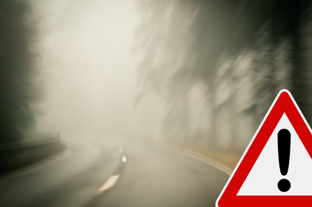Bad weather driving - Foggy morning on a winding country road photo