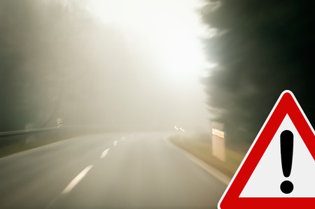 Caution - Foggy morning on a winding country road photo