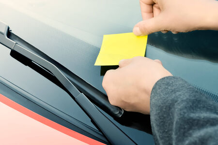 Yellow sticky note on a windshield photo