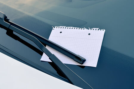 sticky hands: blank sheet of paper under a windshield wiper