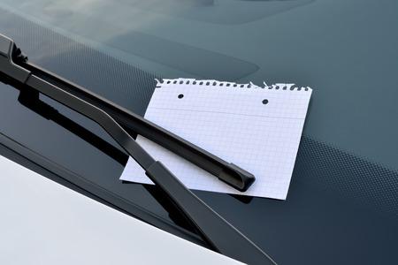 parking space: blank sheet of paper under a windshield wiper
