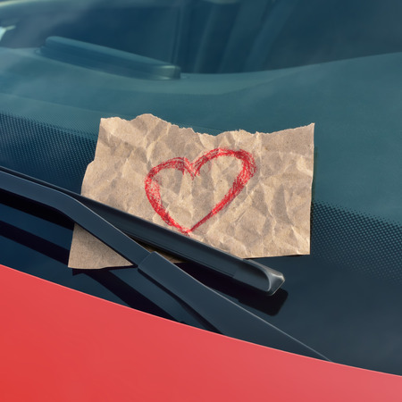 love message: love ticket - drawn heart on a sticky note under a windshield wiper