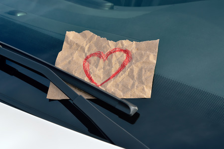 love ticket - drawn heart on a sticky note under a windshield wiper photo