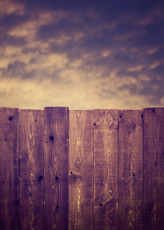 Wooden fence and cloudy sky photo