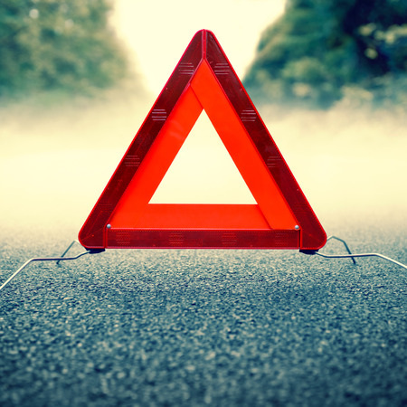 warning triangle: bad weather driving - warning triangle on a foggy road