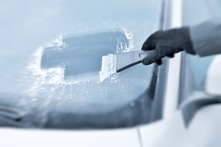 scrape: Winter driving - Scraping ice from a windshield Stock Photo