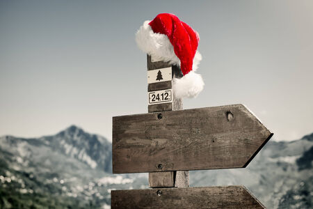 signpost: Signpost with Santa Hat - Signpost with Santa Hat in front of a mountain landscape