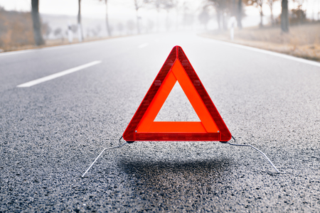 roadside assistance: Bad Weather Driving - Warning Triangle on a Misty Road