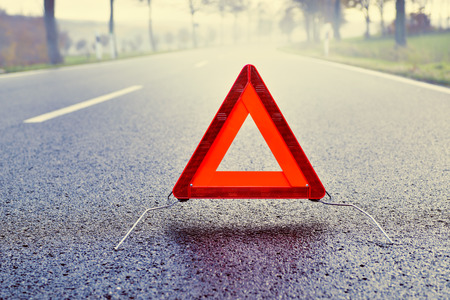 traffic accidents: Bad Weather Driving - Warning Triangle on a Misty Road