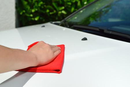 Car care - Car polishing - Polishing a white car with a red cloth. photo
