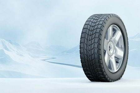 winter tires: Winter tire in front of a snowy mountain landscape.