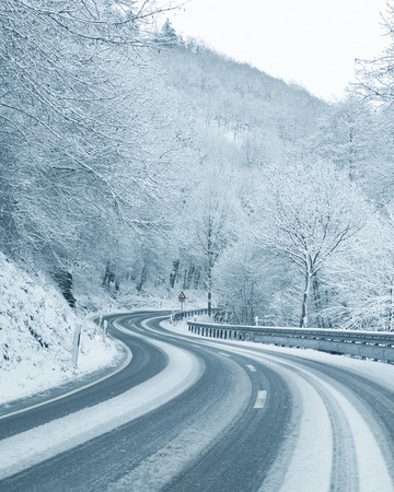 winter tires: Winter Driving - Curvy Snowy Country Road Stock Photo