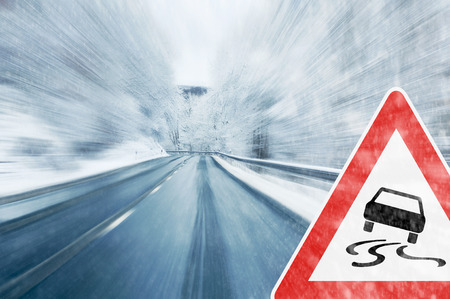 too fast: Winter Driving - Caution - Mountain road with snowfall and traffic sign Stock Photo