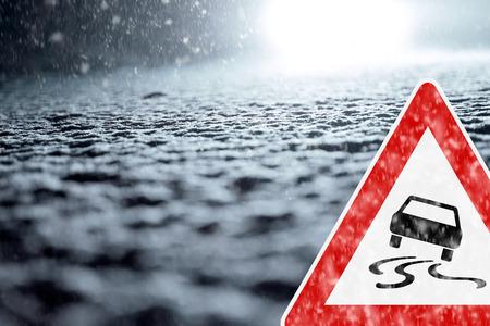冬運転 - 警告標識と冬の道 - 注意雪 - 抽象的な冬背景 - 雪は夜に道路を覆った。